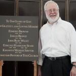 Ken Sawyer next to church plaque